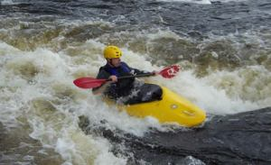 Photo of someone kayaking in a rapids.