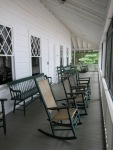 Photo of screen porch with rocking chairs.